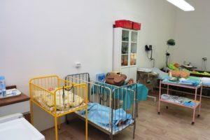 Odborná učebna ošetřovatelství s postýlkami a modely dětských pacientů, porodnickým modelem a kardiotokografem