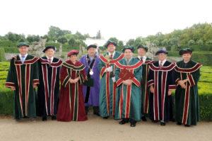 Rektor univerzity, vedení ústavu, pedel a akademičtí pracovníci při promocích